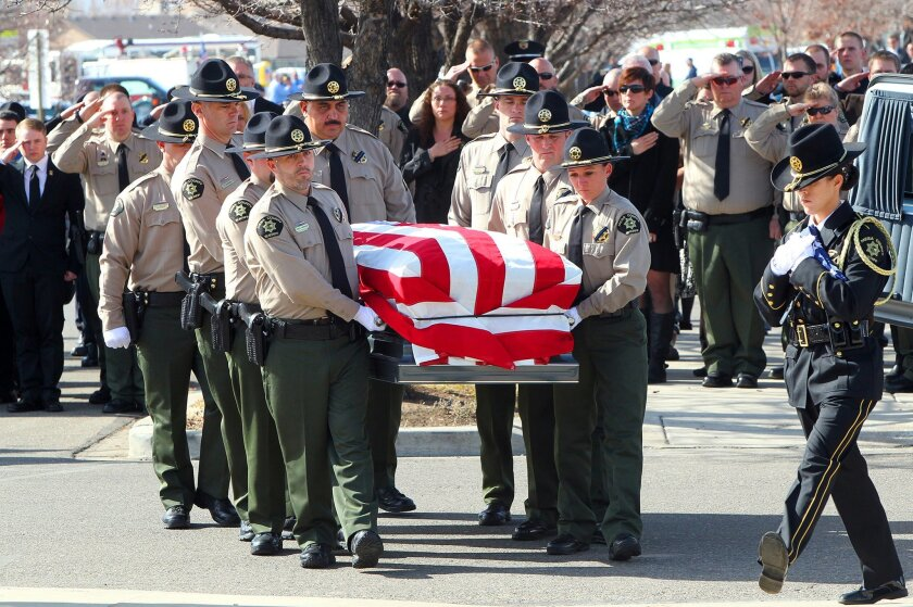 Pallbearers carry the casket bearing the body of Mesa County Sheriff's Department Sgt. Derek Geer on Monday, Feb. 15, 2016, at Canyon View Vineyard Church in Grand Junction, Colo. Geer was shot after responding to a report that a suspicious person carrying a gun and wearing a bandada over his face
