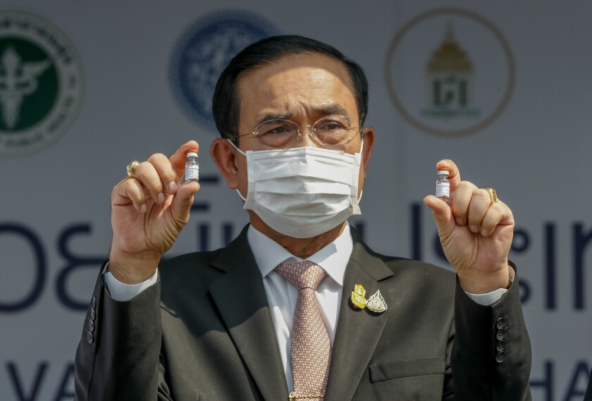FILE - In this Feb. 24, 2021, file photo, Prime Minister Prayuth Chan-ocha holds samples of the Sinovac vaccine during a ceremony to mark the arrival of 200,000 doses in a shipment at the Suvarnabhumi airport in Bangkok. Prayuth on Wednesday, June 16, 2021, declared that the country is planning to fully reopen to foreign visitors without restrictions by mid-October, as the government seeks to restart the crucial tourist industry, heavily hit by the coronavirus pandemic. (AP Photo/Sakchai Lalit, File)