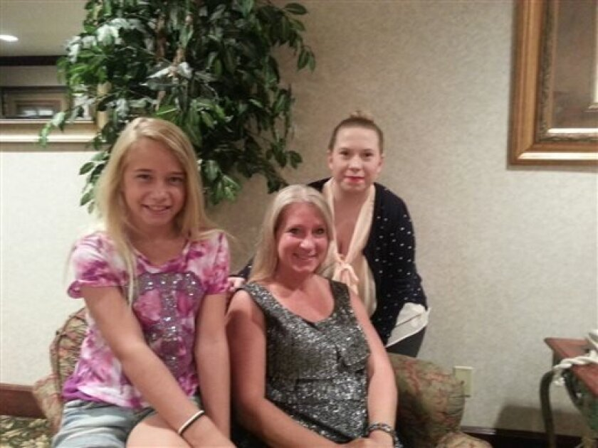 """This photo provided by the family shows, from left, Jolene, Janet and Gabrielle Dunnabeck at their home in Whitney, Texas on Monday, July 1, 2013. The Federal Aviation Administration said Monday it is investigating a close call between a Texas-bound Spirit Airlines flight they were aboard and a skydiving plane that forced the jetliner to dive sharply over Michigan on Sunday evening. """"It was horrifying,"""" Janet Dunnabeck said. """"Every person on that plane was screaming. We thought we were going dow"""