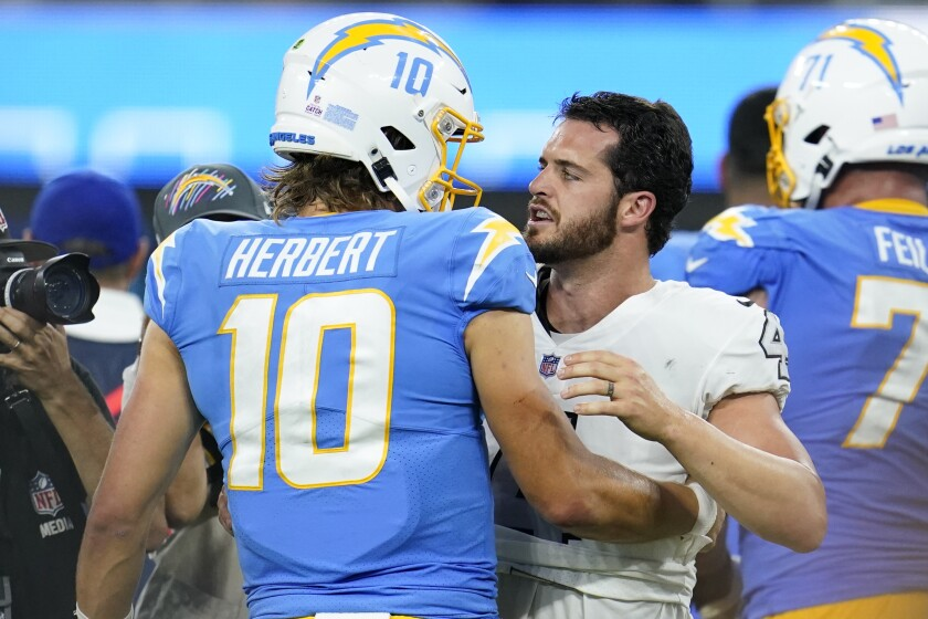 Los Angeles Chargers quarterback Justin Herbert (10) talks with Las Vegas Raiders quarterback Derek Carr after the Chargers defeated the Raiders 28-14 in an NFL football game Monday, Oct. 4, 2021, in Inglewood, Calif. (AP Photo/Marcio Jose Sanchez)