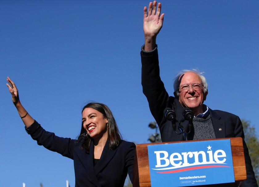 Rep. Alexandria Ocasio-Cortez (D-N.Y.) and Sen. Bernie Sanders (D-Vt.) wave at the crowd.
