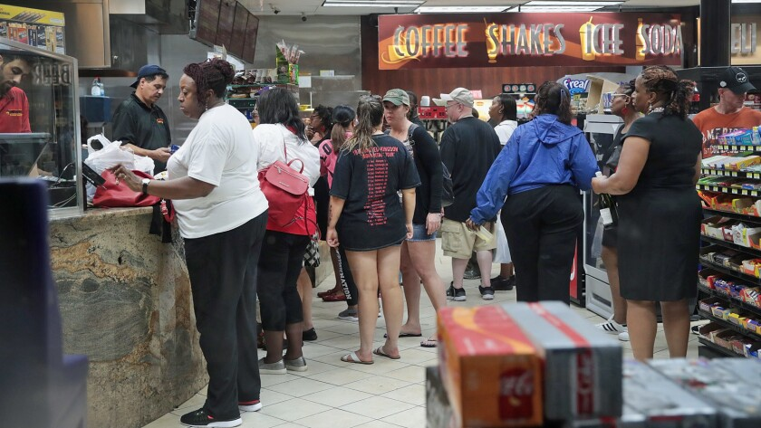 Customers make last-minute purchases Friday at a convenience store near the French Quarter in New Orleans.