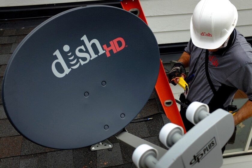 Dish Network and CBS have been negotiating a new carriage agreement to cover CBS-owned television stations. Pictured: Justin Preziosi, field service specialist for Dish Network Corp., installs a satellite television system at a residence in Denver, Colorado.