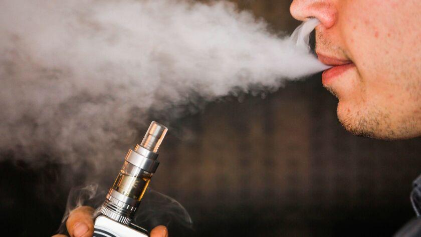 A man smokes an electronic cigarette vaporizer, also known as an e-cigarette, in Toronto