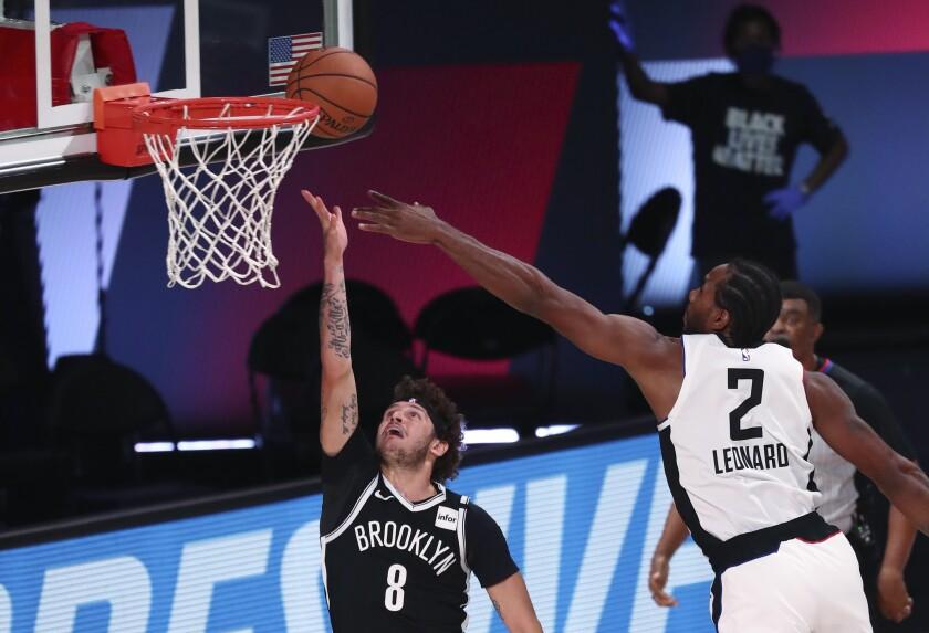 Tyler Johnson, de los Nets de Brooklyn, dispara ante la defensiva de Kawhi Leonard, de los Clippers