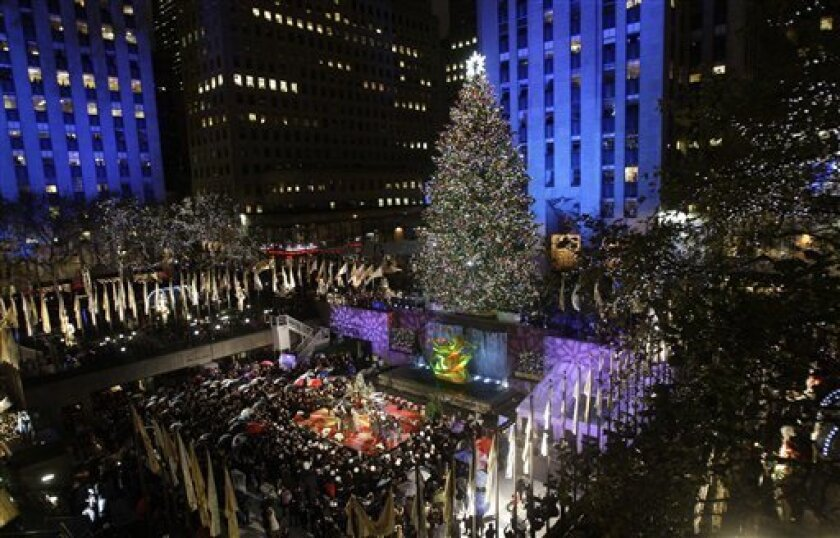 The Rockefeller Center Christmas Tree stands lit in front of the General Electric building in New York's Rockefeller Plaza during the 77th annual tree lighting ceremony Wednesday, Dec. 2, 2009 in New York. (AP Photo/Frank Franklin II)
