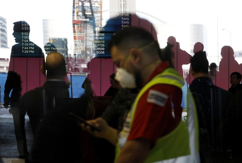 An LAX worker wears a mask amid fears of coronavirus at the Tom Bradley International Terminal at Los Angeles International Airport on Feb. 8