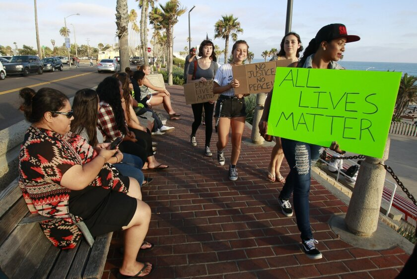"Protesters march past people sitting on a bench as around a dozen people chant ""All lives matter"" on Pacific Street in Oceanside on Thursday."