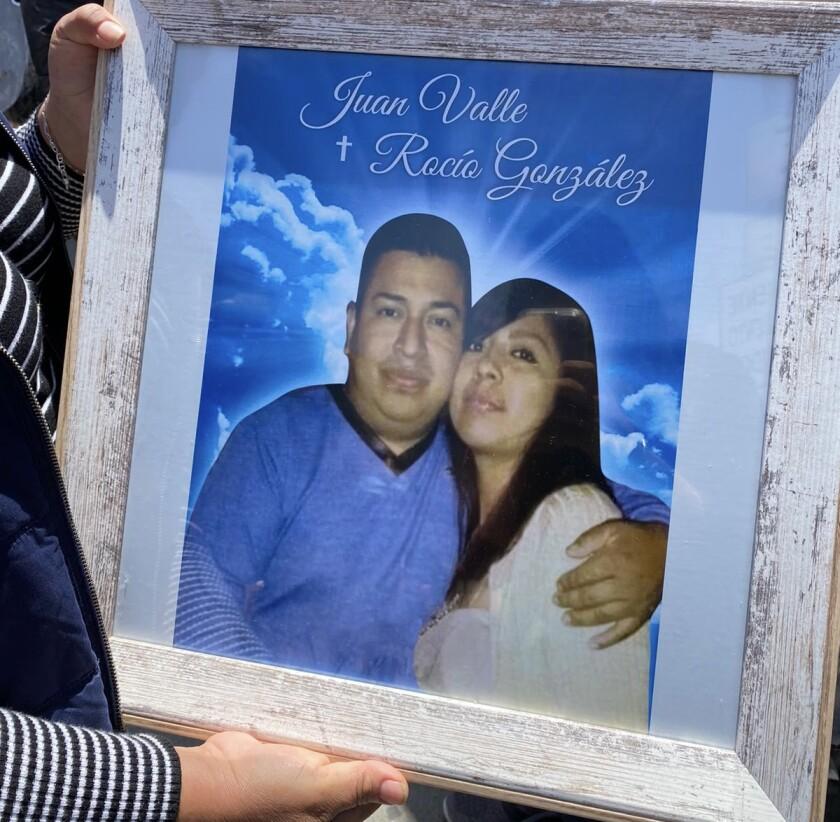 Una mujer no identificada muestra un retrato de Juan Valle y Rocío González frente a una funeraria en Tijuana.