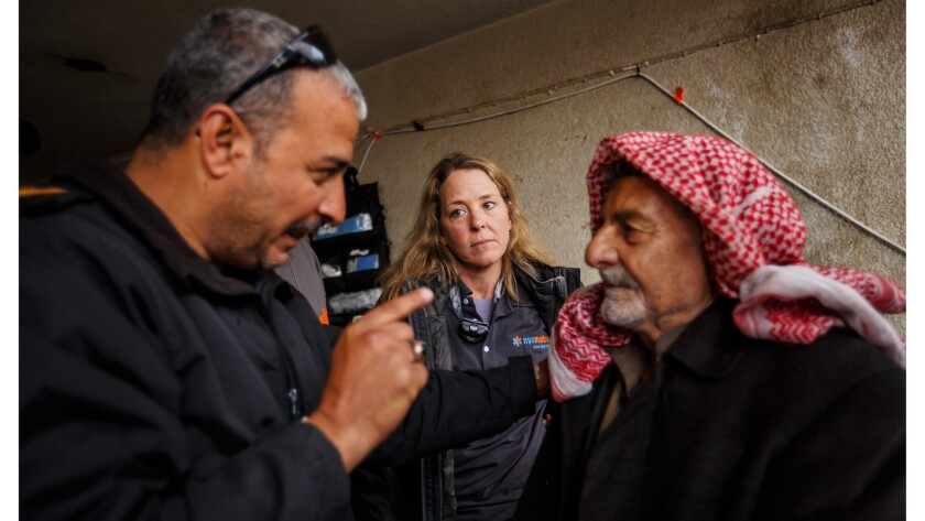 Maj. Tarek Gazali, left, translates the urgency of Kathy Bequary's instructions to go to a hospital to treat the infected burn wound on Jadwaa Hamad, right, that could lead to the loss of his leg.