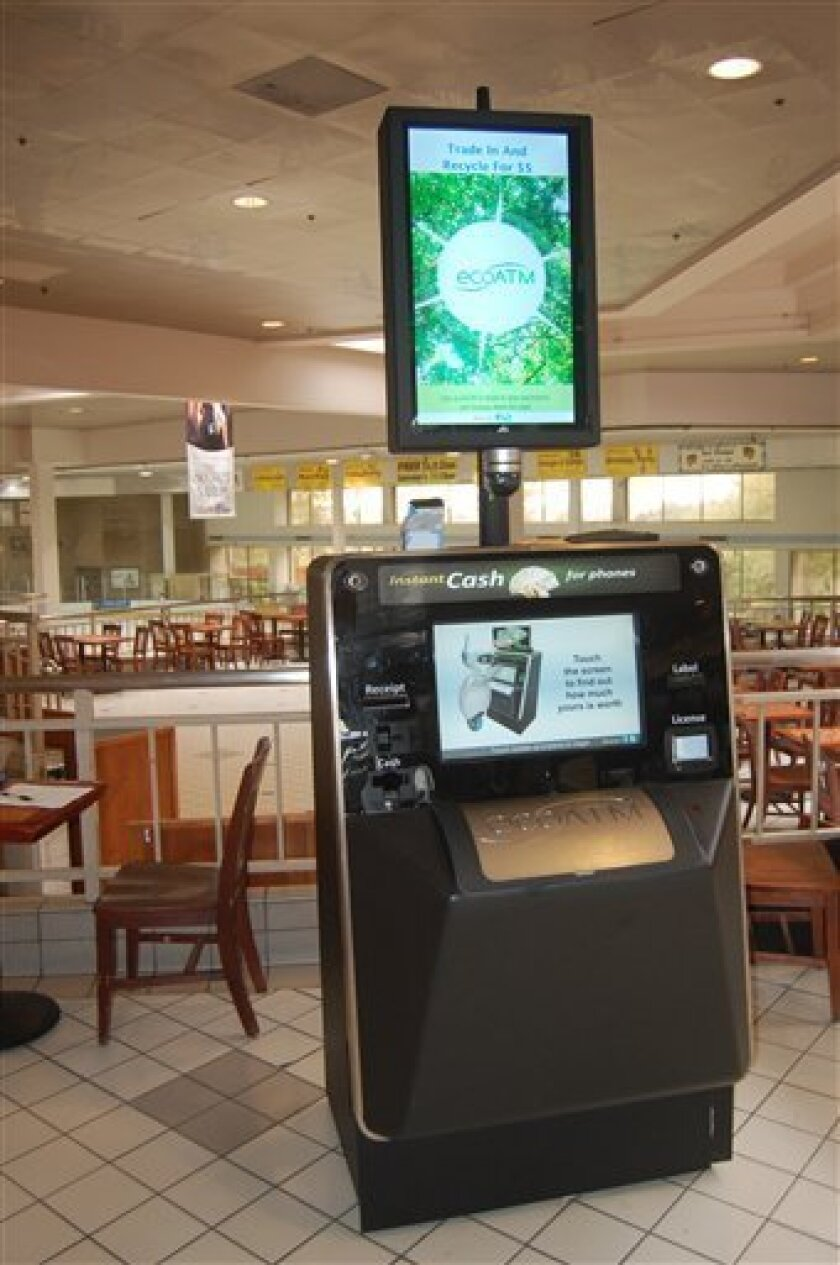 """This undated photograph provided by ecoATM, shows the EcoATM, which is a cupboard-sized machine with a big touch screen and a big metal """"mouth"""" where you can place your old phone or MP3 player. Its analysis complete, it gives you a quote on the spot, based on what a network of hundreds of electronics-recycling companies are willing to pay for it. If you accept, it spits out cash. (AP Photo/ecoATM)"""