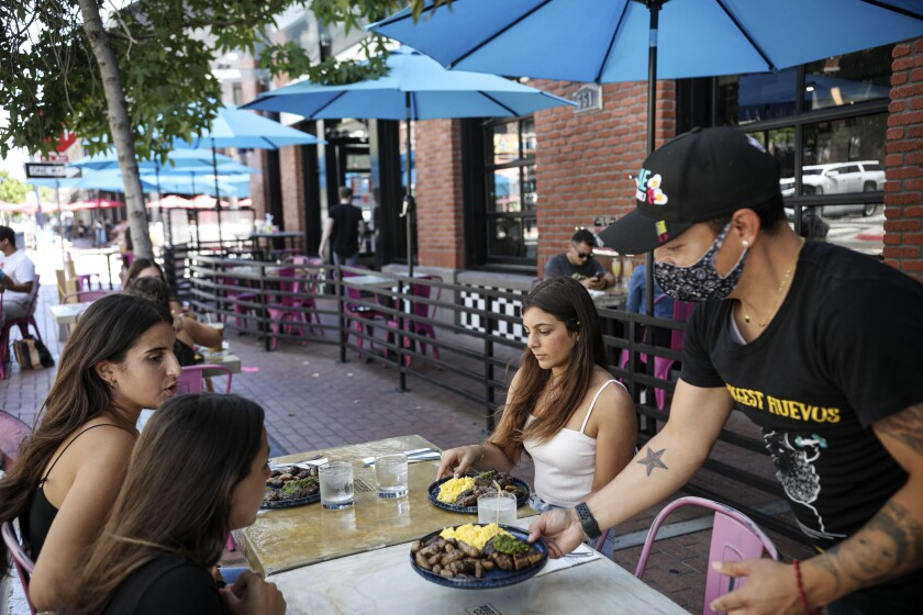 Waiter David Juarez serves customers at Breakfast Company downtown. It received a Paycheck Protection Program loan.