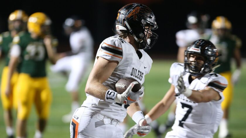 Huntington Beach High's Christian Moore runs in for a touchdown against Edison High during Sunset Le
