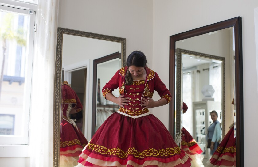Audrey Arellano, 14, of Irvine admires the details of a Mariachi style quinceañera dress at Genesis Bridal Boutique.