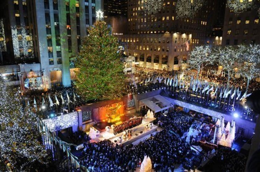 The 74-foot-tall Rockefeller Center Christmas Tree is lit by 30,000 energy efficient LED lights in the 79th annual lighting ceremony, Wednesday, Nov. 30, 2011 in New York. (AP Photo/Henny Ray Abrams)