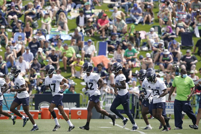 """FILE - Seattle Seahawks defensive players run on the field as fans watch NFL football practice in Renton, Wash., in this Wednesday, July 28, 2021, file photo. It's not exactly everyone into the pool, or gathering around the bonfire. The NFL's """"Back Together Saturday"""" at training camps is all about football. Well, also about having fans return to watch, with all 32 teams conducting open practices on Saturday, July 31, as part of a unified effort by the league. (AP Photo/Ted S. Warren, File)"""