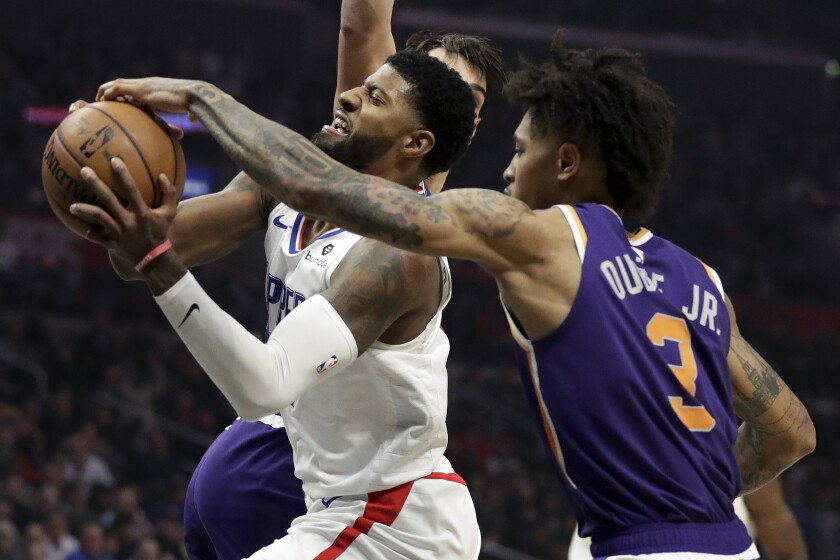 Phoenix Suns forward Kelly Oubre Jr., right, blocks a shot by Clippers forward Paul George.