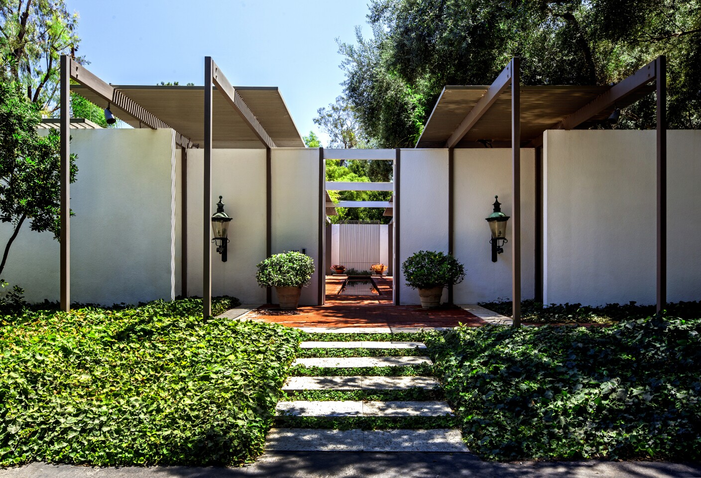 The home's front entrance is flanked by regal lanterns bought in Copenhagen and the yard's two 160-year-old olive trees.(Tim Street-Porter)