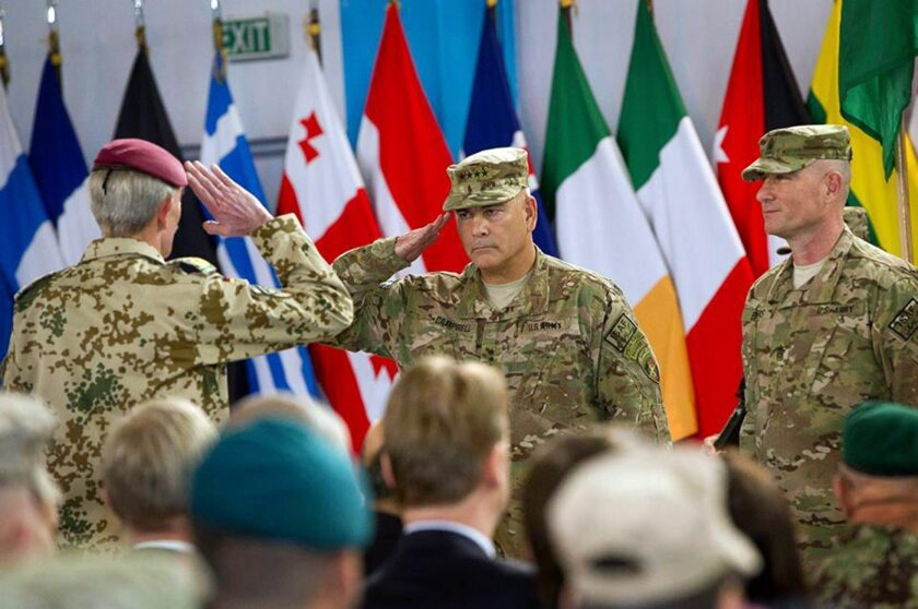 U.S. Gen. John F. Campbell, center, commander of the International Security Assistance Force, salutes during a ceremony in Kabul, Afghanistan, on Sunday marking the end of the coalition's combat mission in the country.