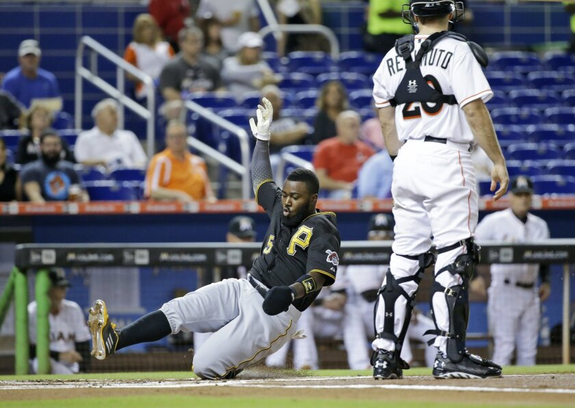 Pittsburgh Pirates' Josh Harrison (5) slides into home to score on a double by Andrew McCutchen as Miami Marlins catcher J.T. Realmuto (20) waits for the throw during the first inning of a baseball game, Wednesday, Aug. 26, 2015, in Miami. (AP Photo/Wilfredo Lee)