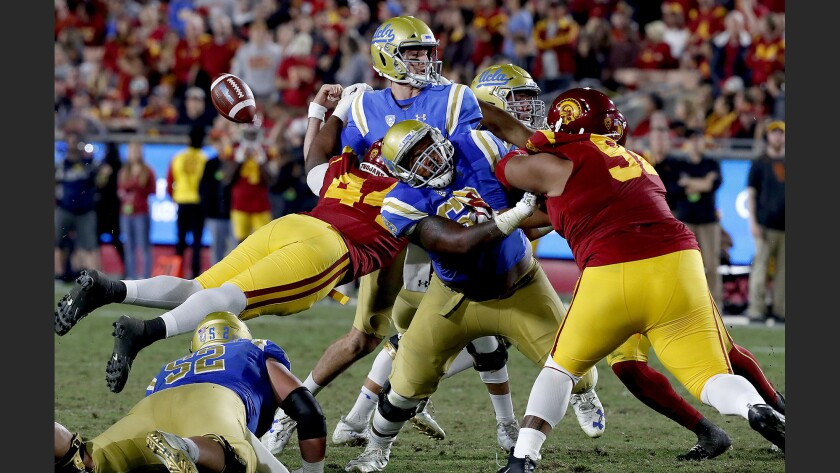 UCLA quarterback Josh Rosen loses control of the ball as the USC defense closes in on him during the second quarter of a game at the Coliseum last season.