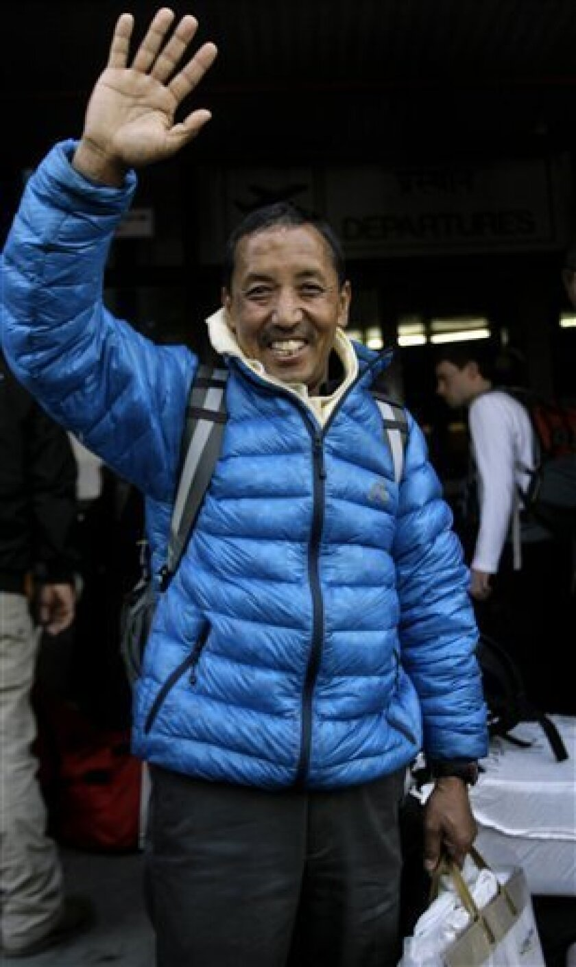 CORRECTS NAME - Nepalese veteran mountaineer Apa, also known as Apa Sherpa, who has climbed Everest a record 20 times, waves to supporters at the airport before leaving for Mount Everest on an expedition to clear away tons of trash left on the world's highest peak, in Katmandu, Nepal, Wednesday, Ap
