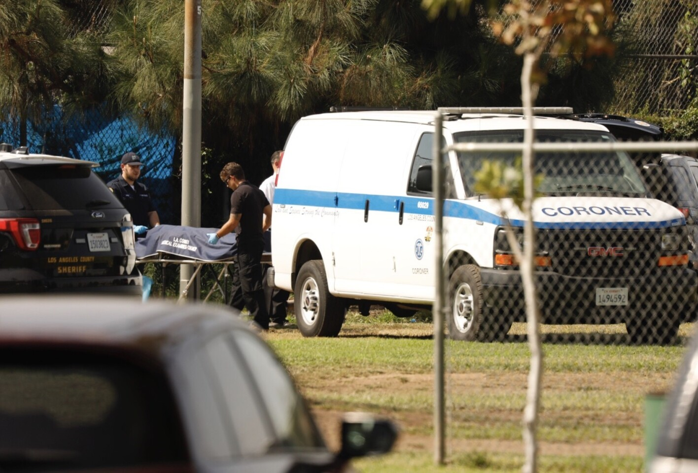 Los Angeles County coroner's officials remove the body of a man killed in a gun battle with sheriff's deputies in East L.A. on Wednesday.