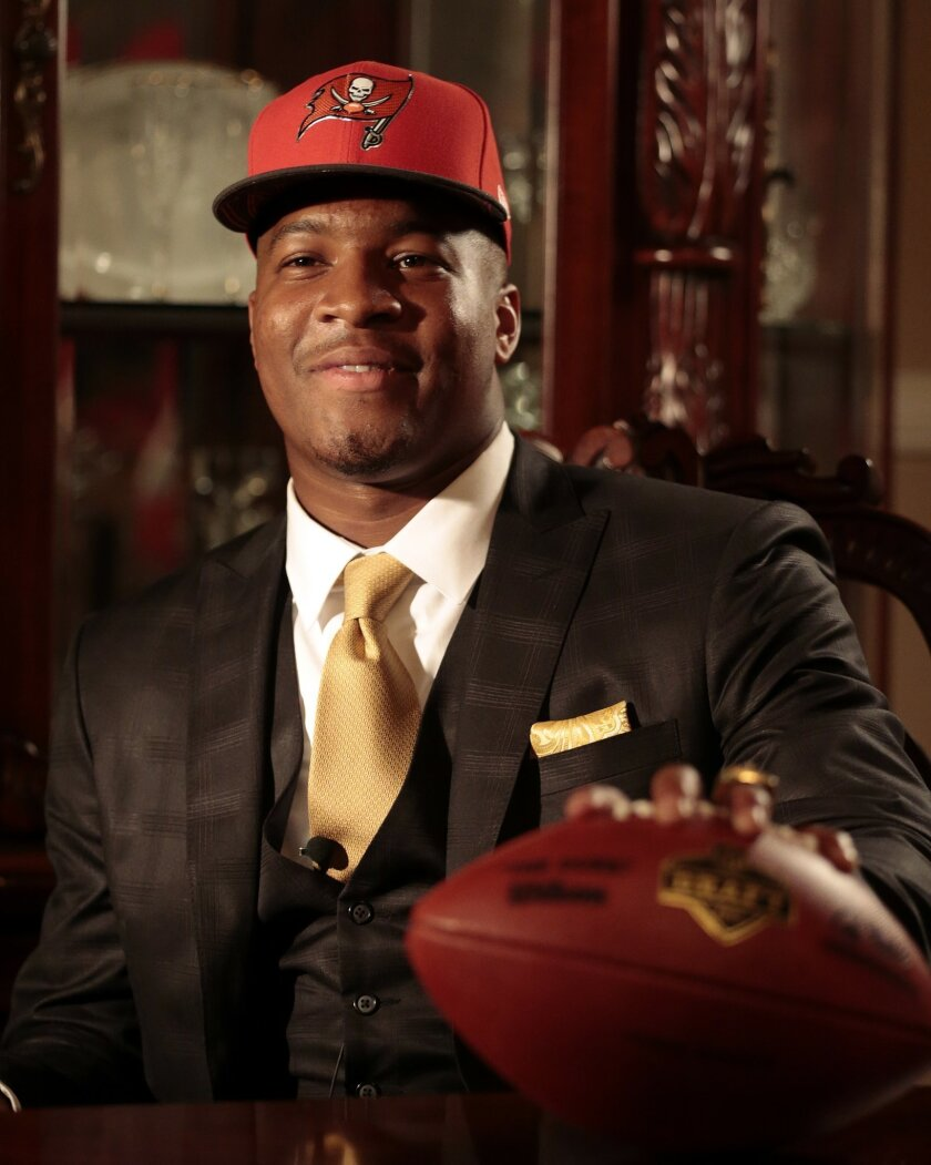 Jameis Winston poses with a Tamp Bay Buccaneers cap and NFL football after he was selected as the number one draft pick, Thursday, April 30, 2015, in Bessemer, Ala. (AP Photo/Butch Dill)