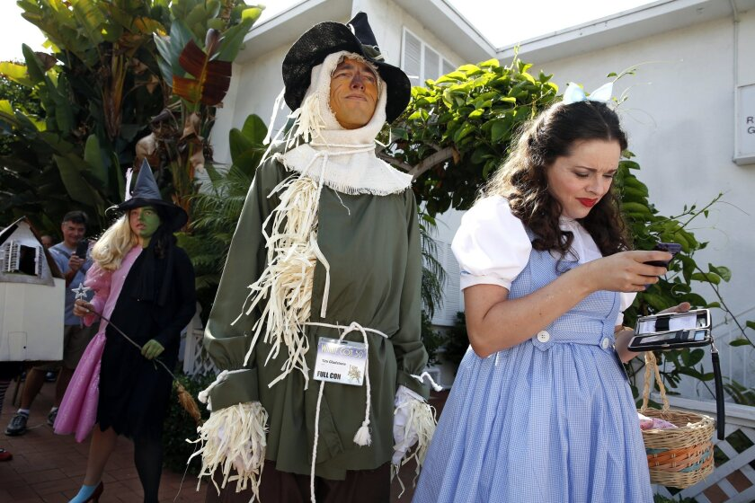 Attendees of Winkie Con 50 which celebrates L. Frank Baum and the Land of Oz, gathered Saturday morning for a costume contest. Contestants included Dorothy (Renee Morton of San Diego), who checked her cell phone. Dorothy was accompanied by the Scarecrow, her friend Tim Gladstone, who stood tall on