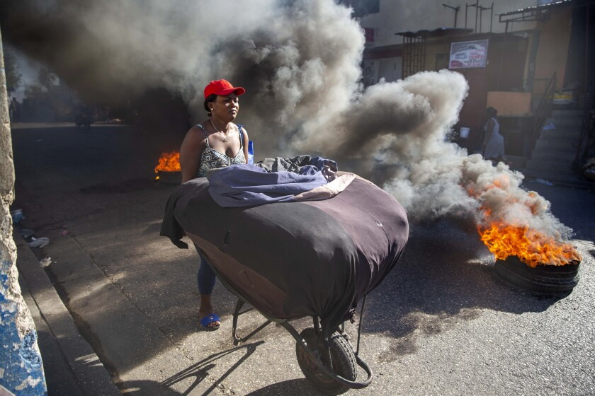 A woman pushes her merchandise away from tires set fire by protesters during a countrywide strike demanding the resignation of Haitian President Jovenel Moise in Port-au-Prince, Haiti, Monday, Feb. 1, 2021. Opposition leaders are pushing for Moïse to step down on Feb. 7 while Moïse has said his term ends in February 2022. (AP Photo/Dieu Nalio Chery)