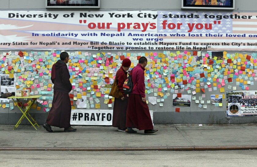 Visiting Nepalese monks, from Mustang Kagbeni, look at a wall of messages of support in Diversity Plaza, in the Jackson Heights neighborhood, in the Queens borough of New York, Thursday, April 30, 2015. In New York, home to the nation's largest Nepalese community, volunteers from the Hyolmo Youth C