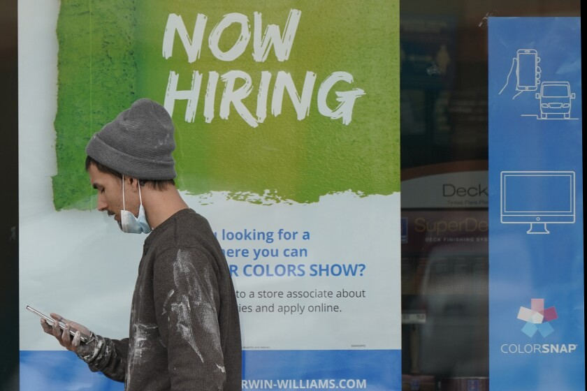 """A man walks past a """"Now Hiring"""" sign on a window at Sherwin Williams store in Woodmere Village, Ohio."""