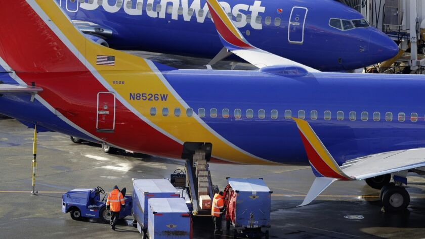 FILE- In this Feb. 5, 2019, file photo Southwest Airlines planes are loaded at Seattle-Tacoma Intern