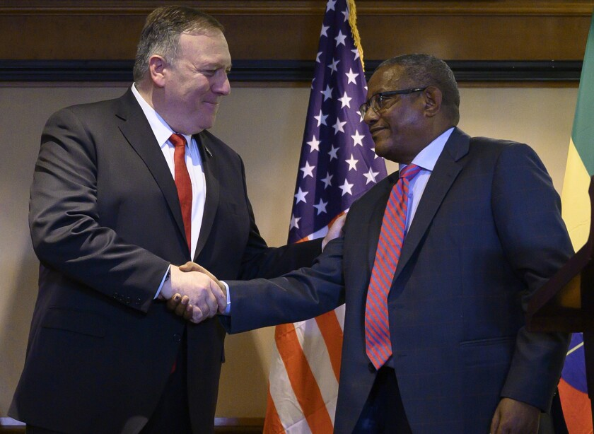FILE - In this Tuesday Feb. 18, 2020 file photo, U.S. Secretary of State Mike Pompeo, left, shakes hands with Ethiopian Foreign Minister Gedu Andargachew, during a joint press conference at the Sheraton Hotel, in Addis Ababa, Ethiopia. In an interview with The Associated Press on Thursday March 12, 2020, Ethiopia's foreign minister said his country is refusing to be pressured by the U.S. into signing a deal with Egypt and Sudan over Ethiopia's controversial dam on the Nile River. (Andrew Caballero-Reynolds/Pool Photo via AP, File)