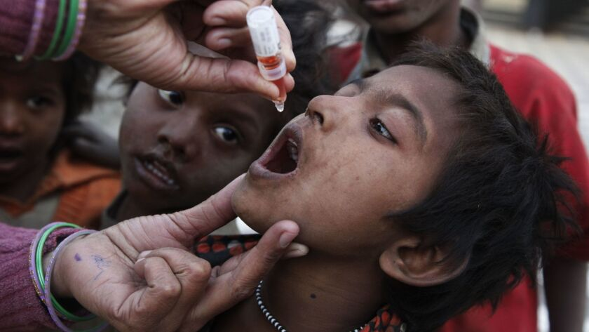 An Indian heath worker administers a drop of polio vaccine to a homeless child at a railway station
