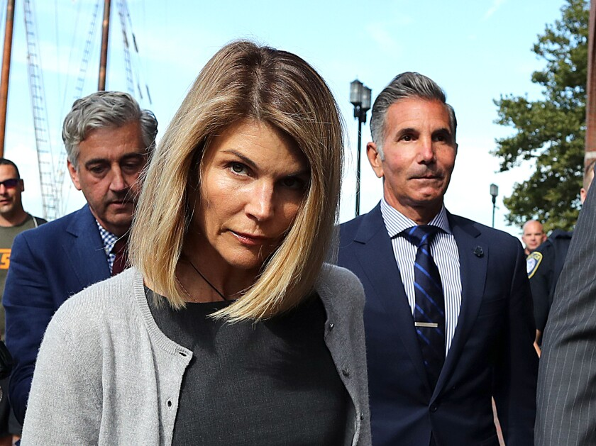 Lori Loughlin and her husband Mossimo Giannulli, right, leave the courthouse in Boston