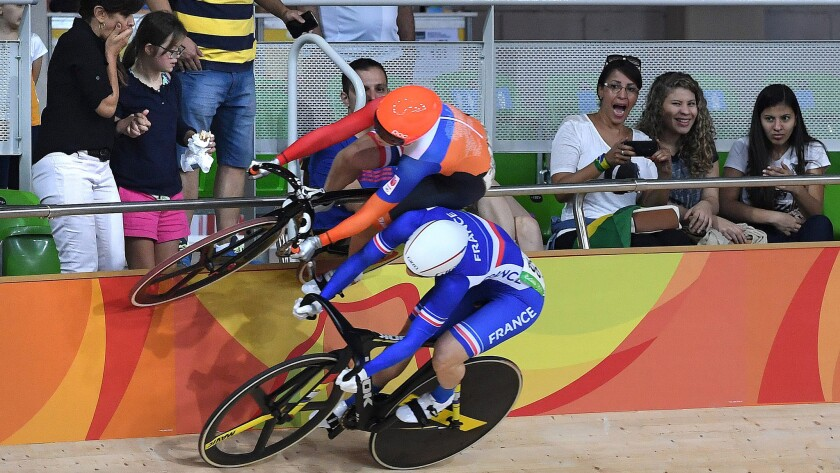 Lauren van Riessen of the Netherlands rides on the wall next to France's Virginie Cueff to avoid a crash during a heat in the women's keirin competition on Saturday.