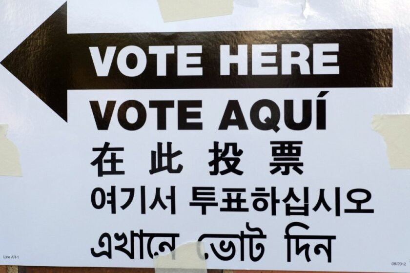 """A sign is posted outside an election site in New York City that reads """"Vote Here"""" in English, Spanish, Chinese, Korean and Bengali."""