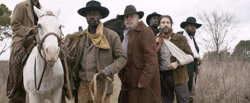 """David Gyasi, holding horse, and Ron Perlman in the movie """"Hell on the Border."""""""