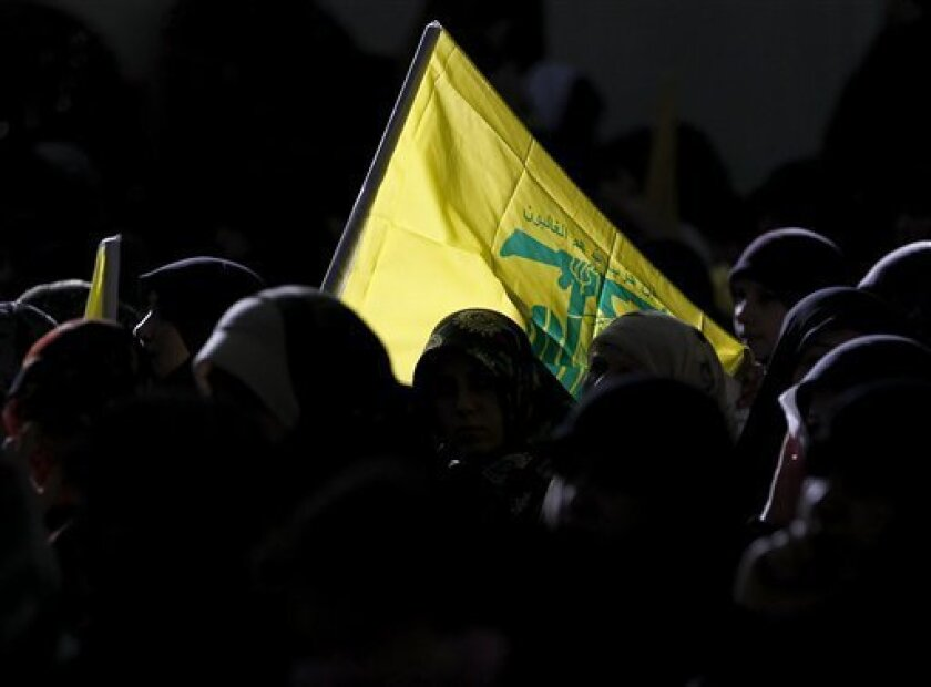 Lebanese woman, supporters of Hezbollah, carry the group's yellow flag as they listen to the speech of Hezbollah leader Hassan Nasrallah in the occasion of Jerusalem Day in the southern suburb of Beirut, Lebanon, Friday, Sept. 3, 2010. Hezbollah leader says he will not respond to a U.N.-appointed prosecutor's demand for his group to hand over all information relevant to the assassination case of former Lebanese Premier Rafik Hariri. Sheik Hassan Nasrallah says the group is ready to cooperate instead with the Lebanese judiciary. (AP Photo/Hussein Malla)