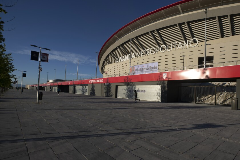A man jogs past Atletico Madrid's Wanda Metropolitano stadium in Madrid, Spain, Tuesday, May 5, 2020. The Spanish soccer league aims to restart in June without spectators. It's new compulsory protocols say all players, coaches and club employees must be tested for COVID-19 coronavirus before training resumes, then regularly after that. All clubs' training facilities must be properly prepared and disinfected before players can start practicing individually. (AP Photo/Paul White)