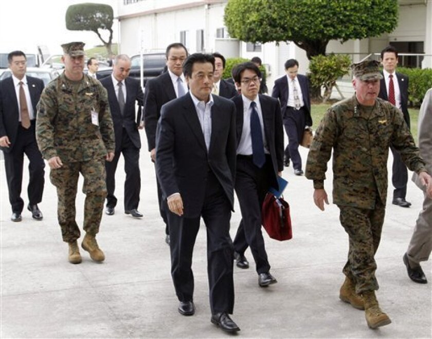 Japanese Foreign Minister Katsuya Okada, center, visits Camp Foster in Okinawa, Japan, during his inspection tour Saturday, Dec. 5, 2009. Okada toured the southern island of Okinawa to meet with local officials to work out a compromise over the relocation of the Marine Corps Air Station Futenma, a major U.S. Marine base, that has become the center of a dispute with Washington. (AP Photo/Kyodo News)