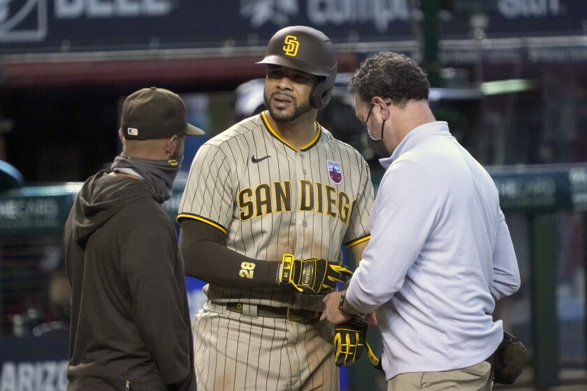 Padres' Tommy Pham, center, talks with manager Jayce Tingler and athletic trainer Mark Rogow after injuring his hand Sunday.