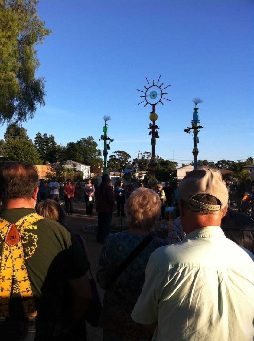 Dozens gather around Dr. Sharon Lund for a saging and open ceremony at the newly opened water-conservation garden. In the background are artist Vicki Leon's translucent solor totems, crafted from mostly repurposed and disposable substances.
