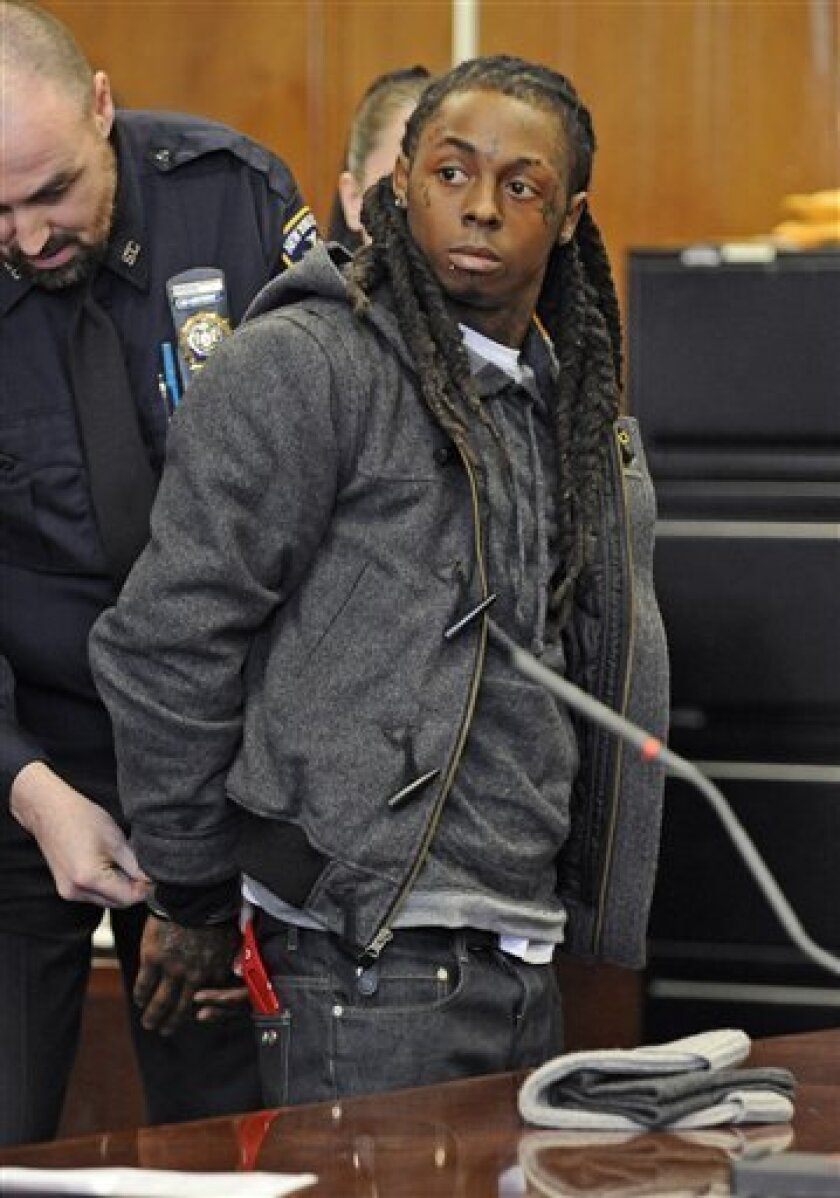 "FILE -- In a March 8, 2010 file photo Rapper Lil Wayne is handcuffed at Manhattan criminal court in New York. Lil Wayne was moved Monday Oct. 4, 2010, into ""punitive segregation for breaking jail rules.(AP Photo/ Louis Lanzano/file)"