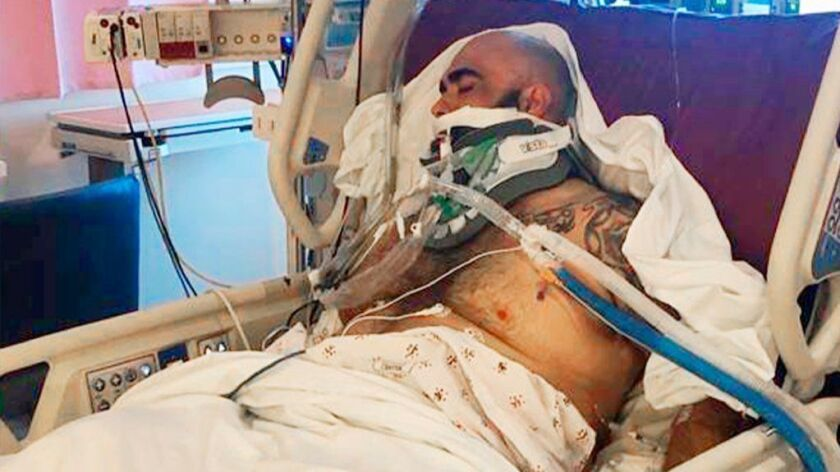 Rafael Reyna in his hospital bed at Los Angeles County-USC Medical Center after he was severely injured in an altercation outside Dodger Stadium.