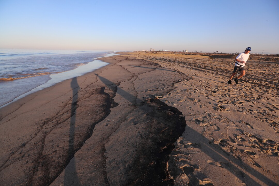 A jogger on the beach bordering Newport and Huntington Beach Sunday morning