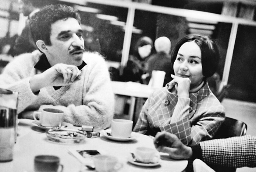 A black-and-white photo of Gabriel García Márquez and Mercedes Barcha in the late 1960s, seated at a table with coffee cups.