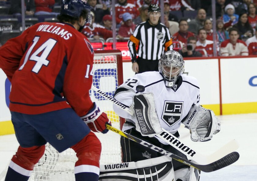 Los Angeles Kings goalie Jonathan Quick (32) deflects the puck off his shoulder with Washington Capitals right wing Justin Williams (14) nearby, in the first period of an NHL hockey game, Tuesday, Feb. 16, 2016, in Washington. (AP Photo/Alex Brandon)