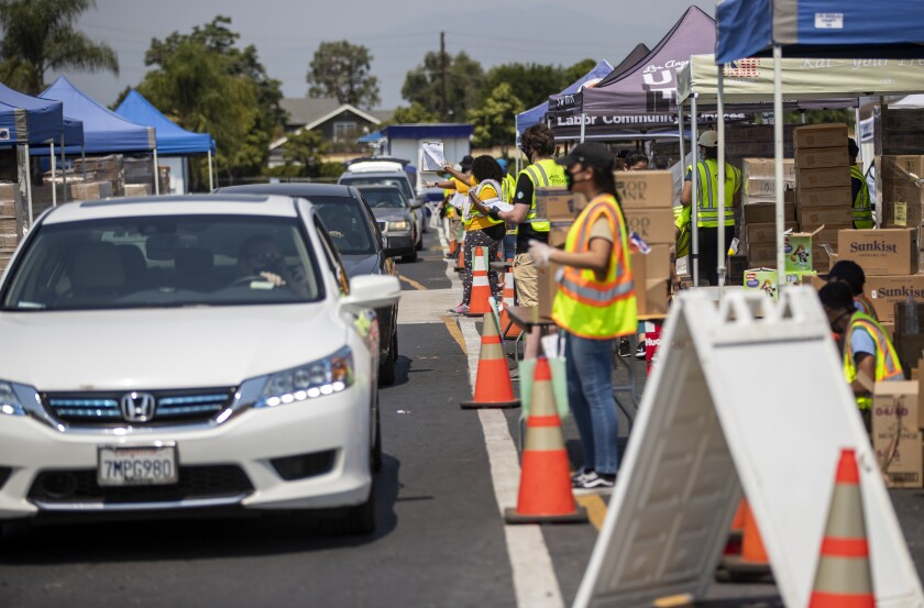 Cars are lined up to collect boxes of food at a food bank in Pomona in August. (Gina Ferazzi / Los Angeles Times)